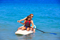 Embrome a la muchacha de la persona que practica surf de la resaca de la paleta con fila en la playa Imágenes de archivo libres de regalías