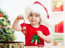 Embrome a la muchacha en el sombrero de Papá Noel que sostiene las galletas de la Navidad Imágenes de archivo libres de regalías