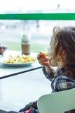 Embrome a la muchacha en un restaurante que come los alimentos de preparación rápida Fotos de archivo libres de regalías