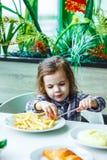 Embrome a la muchacha en un restaurante que come los alimentos de preparación rápida Fotografía de archivo