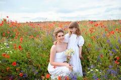 Embrome a la muchacha que abraza a su madre entre las flores del campo Imagen de archivo libre de regalías