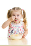Muchacha del niño que come las avenas con leche Fotos de archivo