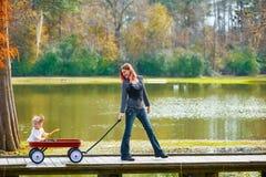 Embrome la muchacha y a la madre que caminan en el lago con el carro del tirón Imagen de archivo libre de regalías