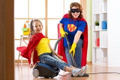 Embrome la muchacha y sus trajes weared madre del super héroe El niño y la mujer lindos del ayudante hacen el sitio de limpieza y Fotografía de archivo