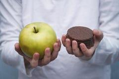 Embrome las manos del ` s con la galleta del chocolate y la manzana verde Opción dura entre la comida sana y malsana Fotografía de archivo libre de regalías