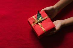 Embrome las manos que sostienen la caja de regalo de papel en fondo rojo Fotografía de archivo libre de regalías