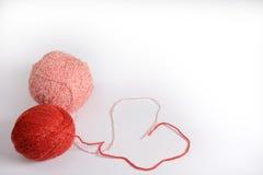 Embrouillement de rouge et de rose des fils de tricotage sur un fond blanc Image stock