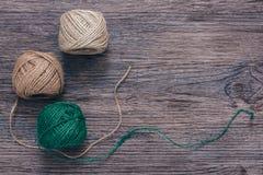 Embrouillements verts et beiges de fil sur une surface en bois Fil de toile Photo libre de droits