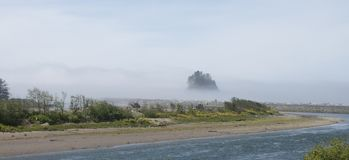 Embrumez le roulement dans au-dessus de l'estuaire et de la forêt de pin d'arbre dessus photographie stock libre de droits