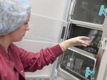 Embryologist die steekproef zet in incubator Stock Fotografie