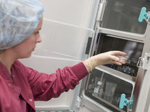 Embryologist putting sample into incubator. In laboratory Stock Photography