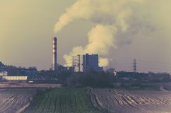 Embudos que fuman de una central eléctrica cerca de tierras de labrantío fotografía de archivo