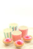 Emepty round muffin cups and pink cakes Royalty Free Stock Images