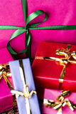 Emerald Bowknot over Magenta Gift Box. Close-up shot of a green bow tied around a magenta packet. Four smaller gift boxes with golden ribbons. All wrapped for Royalty Free Stock Photography