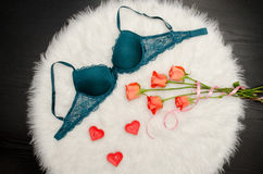 Emerald bra with lace on white fur. Orange roses, heart shaped candles. Fashionable concept. Top view Stock Photography