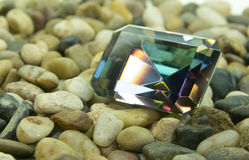 Emerald Cut Faceted Gemstone. Emerald cut faceted mystic topaz gemstone on a bed of rocks Stock Image