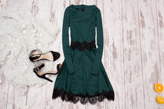 Emerald dress with lace, black shoes and a Imitation fur on a wooden background, fashionable concept Stock Photos