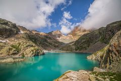 Emerald Green Lac Blanc Altitude Lake on a Sunny Day. Emerald Green Altitude Lake on a Sunny Day with Cloud Blue Sky Royalty Free Stock Photo