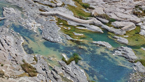Emerald green pools of water in pockets of eroded rock formation Stock Photo