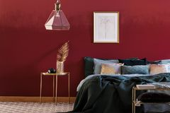 Emerald green and red bedroom. Emerald green bed against red wall with poster in bedroom interior with lamp above gold table royalty free stock images