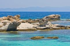 Emerald green sea water at coast of small uninhabited island near coast of Sithonia Stock Images