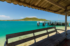 Emerald green water and blue sky with jetty Stock Images