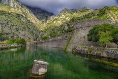 Emerald green waters of Kotor Bay or Boka Kotorska and the ancient wall of Kotor former Venetian fortress in Montenegro. Emerald green waters of Kotor Bay or stock photography
