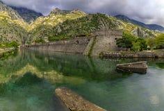 Emerald green waters of Kotor Bay or Boka Kotorska and the ancient wall of Kotor former Venetian fortress in Montenegro. Emerald green waters of Kotor Bay or stock images