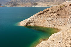 Emerald green waters of a lake against a brown arid shore royalty free stock photography