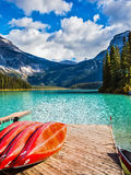 Emerald Lake in the Canadian Rockies. The concept of active tourism and vacation. Emerald Lake in the Canadian Rockies. Shiny red kayaks are dried upside down stock photo
