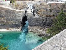 Emerald Lake Rock Crevice. Rock crevice forming natural bridge over crystal blue emerald water near Emerald Lake, Yoho National Park, Canada Stock Image