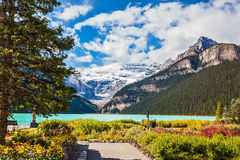 The emerald lake surrounded by glaciers and pine forests Stock Photo