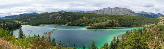 Emerald Lake under cloudy sky in Yukon Canada. Emerald Lake at falls with mountains afar, surrounded by trees, in Yukon, Canada Royalty Free Stock Photos