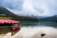 Floating canoe on the water of emerald lake Stock Photos