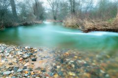 Emerald River in the Forest. A river reflecting emerald colors, following a curvy path into the forest stock photos