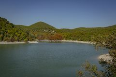 Emerald water of a lake in Sukko, against the background of a mountain covered with forests. Natural beauty of the resort near Anapa. Nature concept for design stock images