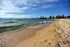 Emerald wave breaking on golden sand beach in Lake Tahoe Royalty Free Stock Photography
