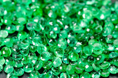 Emeralds, lots of. Large pile of green emeralds on black stone Royalty Free Stock Image