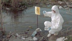 Emergencia del Biohazard en la naturaleza, trabajador del hazmat en el uniforme que recoge la muestra infectada de agua en los tu almacen de video