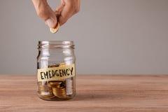 emergency Βάζο γυαλιού με τα νομίσματα και μια έκτακτη ανάγκη επιγραφής Το άτομο κρατά το νόμισμα στο χέρι του στοκ εικόνα με δικαίωμα ελεύθερης χρήσης