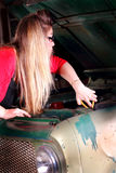 Emergency. A pretty young college beauty with long straight blond hair has an emergency and is working on a vehicle. Shallow depth of field Royalty Free Stock Image