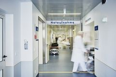 Emergency admission entrance hospital doctor wheelchair. Emergency admission entrance hospital with doctor wheelchair and patient in motion blur in the corridor royalty free stock images