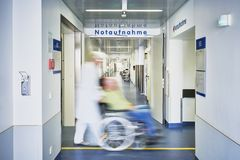 Emergency admission entrance hospital doctor wheelchair patient. Emergency admission entrance hospital with doctor wheelchair and patient in motion blur in the stock photo