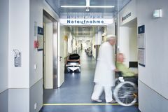 Emergency admission hospital doctor wheelchair patient. Emergency admission entrance hospital with doctor wheelchair and patient in motion blur in the corridor stock images