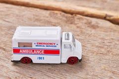 Emergency ambulance on wooden background. Royalty Free Stock Photo