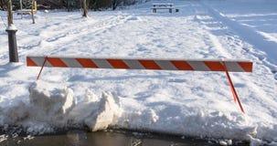 Emergency barrier blocking snowed recreation zone. Striped emergency barrier blocking snowed recreation zone Royalty Free Stock Image