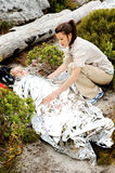 Emergency blanket. A women is injured while hiking outdoors. her friend has covered her with and emergency blanket and checks on her using a first aid kit royalty free stock image