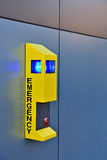 Emergency call box. A yellow emergency call box on the side of a building Royalty Free Stock Photo