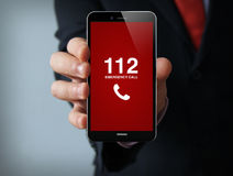 Emergency call businessman smartphone. Emergency concept: businessman hand holding a 3d generated touch phone with emergency call on the screen. Screen graphics Royalty Free Stock Photography