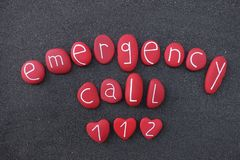 Emergency Call 112 text with red colored stones over black volcanic sand. Unique sign with red colored stones over black volcanic sand for emergency call 112 stock photo